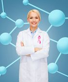 healthcare and medicine concept - smiling female doctor with pink cancer awareness ribbon over molec