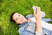 lifestyle, summer vacation, technology and people concept - smiling young girl with smartphone lying