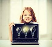 education, school, technology and internet concept - little student girl pointing at laptop pc with
