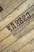 Numbers and letters written with paint on wood.