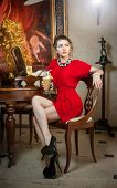 Fashionable attractive young woman in red dress sitting in restaurant. Beautiful lady posing