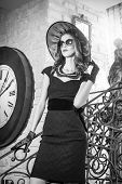 Young beautiful brunette woman in black standing on stairs near an over sized wall clock. Elegant