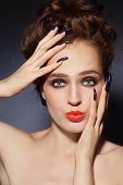 Young beautiful woman with stylish hairdo, long nails, bright lips and funny expression