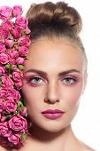 Portrait of young fresh beautiful woman with hair bun and pink roses near her face over white background