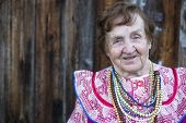 Elderly woman in ethnic clothes, outdoors. With space for your text.