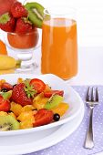 Fresh fruits salad on plate with berries and juice on light background