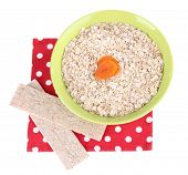 Oatmeal in a green bowl with dried apricots and crisp bread on a red polka dot napkin isolated on wh
