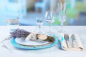 Dining table setting with lavender flowers on table, on bright background