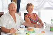 stock photo of elderly couple  - Smiling elderly married couple having breakfast at restaurant near window - JPG