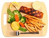 Spicy grilled salmon steak with steamed vegetables, french fries, lemon wedges and tartar sauce. Served on cutting board. Isolated, high angle view.