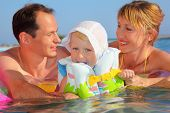 Happy Family With Little Girl In White Hat And Lifejacket Bathing In Pool Against Sea