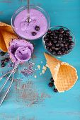 Tasty ice cream with fresh berries on old blue wooden table
