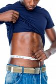 Mid section of a fit young man measuring waist over white background