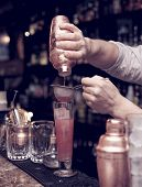 Bartender is straining cocktail in highball glass, toned image