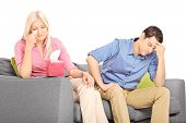 Woman crying after an argument with her boyfriend seated on couch isolated on white background