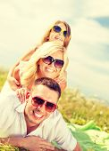 summer holidays, family, child and happy people concept - smiling family in sunglasses lying on blan