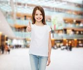 advertising, childhood, gesture, consumerism and people - smiling girl in white t-shirt showing thum