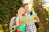 travel, vacation, tourism and friendship concept - smiling couple with map and backpack in forest
