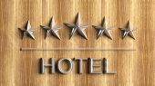 Five silver stars and word Hotel on wood