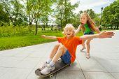 Small girl pushing happy boy on skateboard