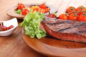 fresh rich juicy grilled beef meat steak fillet with marks on wooden plate over table decorated with