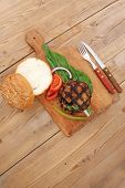 extra thick hot beef meat hamburger lunch on wooden plate with tomatoes and salad over wooden  table