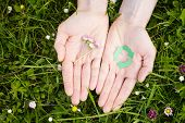 image of reuse recycle  - Open hands of a woman hold freshly picked flowers and a green recycling symbol - JPG