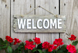 picture of wooden fence  - Weathered welcome sign hanging on wooden fence with flower border of red roses - JPG