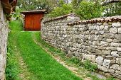 foto of old stone fence  - Old Wooden Gate and Stone Fence in Old Town - JPG