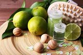 Spa composition with lime on wooden plate and wooden table background