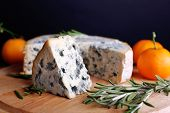 Blue cheese with sprigs of rosemary and oranges on wooden board and dark background