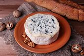 Blue cheese on earthenware dish with nuts and baguette on burlap cloth and wooden table background