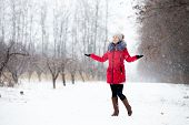 Happy Smiling Female In Red Winter Jacket Enjoys The Snow, Outdoors, In Park