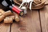 Red wine bottle, heap of corks and corkscrew over rustic wooden table background with copy space