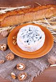 Blue cheese on earthenware dish with nuts, baguette and hay on burlap cloth and wooden table background