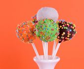 stock photo of cake pop  - Sweet cake pops in vase on orange background - JPG