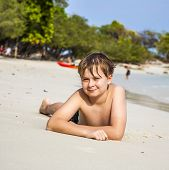 Boy Lies At The Sandy Beach And Enjoys The Fine Warm Sand