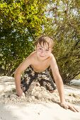 Happy Young Boy Is Digging In The Sand Of The Beach
