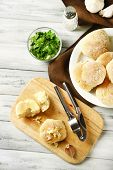 Fresh homemade bread buns from yeast dough on wooden tray, on color wooden background