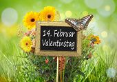 An image of a little chalkboard in the garden with the text 14th of february Valentines Day in german language