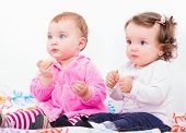 image of teething baby  - Photo of two adorable baby sitting on the bed and nibbles - JPG