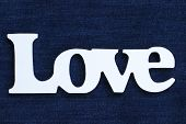 stock photo of indigo  - Wooden Love text on indigo blue denim texture background - JPG