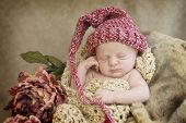 picture of newborn baby girl  - A sleeping newborn baby girl in chocetted cocoon wearing hat with vintage looking setup selective focus with focus on face - JPG