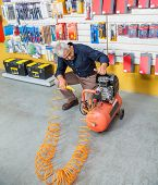picture of air compressor  - Full length of senior man examining air compressor in hardware shop - JPG