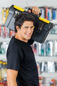 Side view portrait of confident man carrying toolbox on shoulder in hardware store