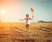 foto of windmills  - cute little girl in summer day holds windmill in hand - JPG