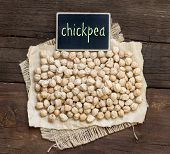 stock photo of chickpea  - Chickpea with a small chalkboard on a wooden table - JPG