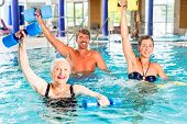 Group of people, mature man, young and senior women, at water gymnastics or aquarobics