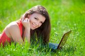 Young woman with laptop sitting on green grass.