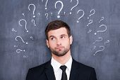 image of adults only  - Confused young man standing against blackboard with question marks - JPG